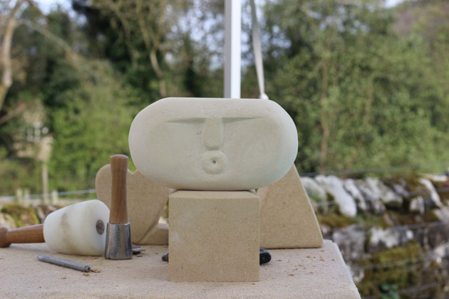 Pebble shaped face carved in stone