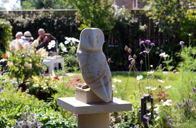 Owl sculpture among flowers