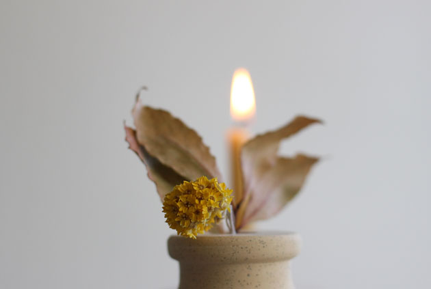 Natural beeswax candle in stone holder